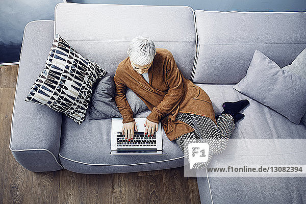 Woman using laptop while relaxing on sofa at home