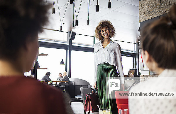 Glückliche Frau schaut Kollegen im Cafe an