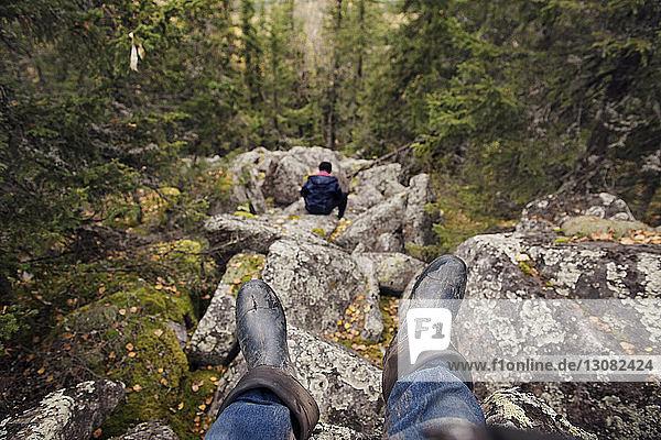 Auf Felsen sitzender Wanderer im Wald