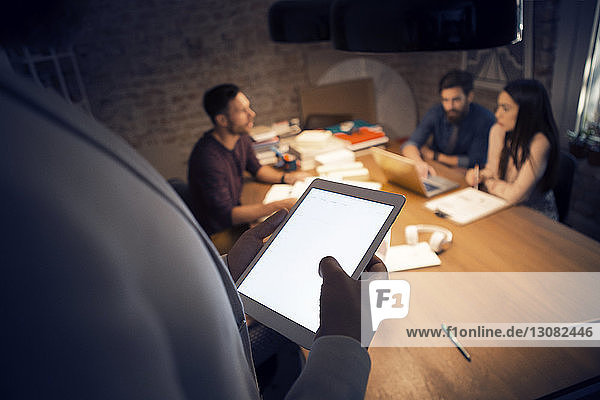 Cropped image of businessman using tablet computer while colleagues discussing in background