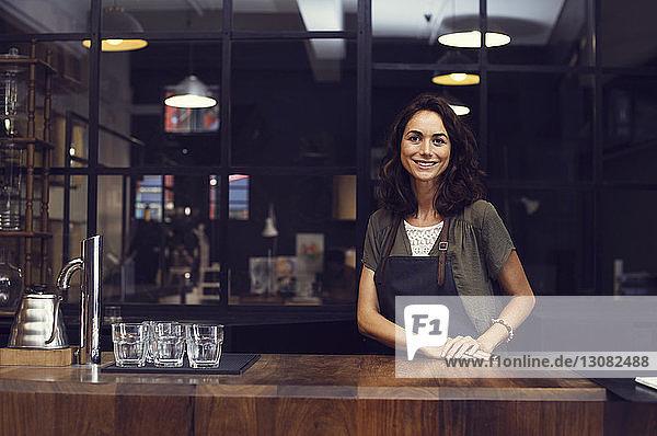 Porträt einer glücklichen Besitzerin im Café stehend