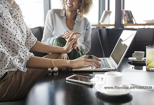 Midsection of businesswoman working on laptop while sitting by colleague at cafe