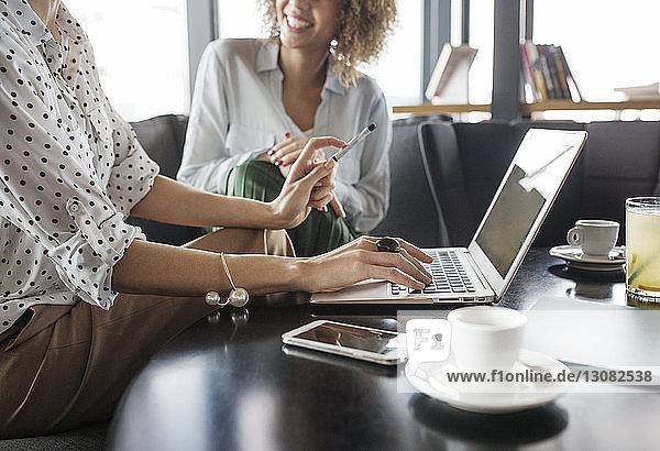 Mitschnitt einer Geschäftsfrau  die am Laptop arbeitet  während sie neben einem Kollegen im Café sitzt