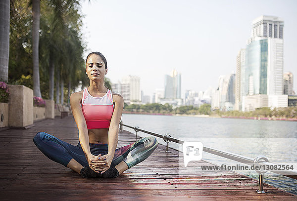 Woman sitting and stretching in butterfly position on wooden walkway by river