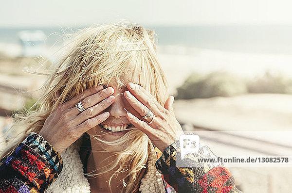 Glückliche junge Frau bedeckt Augen am Strand Glückliche junge Frau bedeckt Augen am Strand