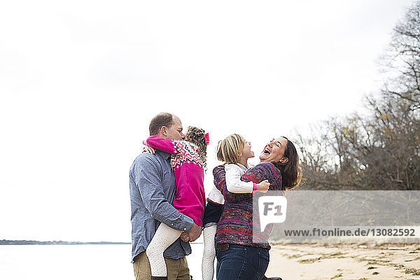 Happy parents embracing daughters at beach against clear sky