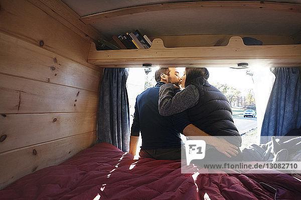 Rückansicht eines Pärchens  das sich küsst  während es im Wohnmobil auf dem Bett sitzt
