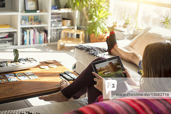Girl looking at pictures in tablet computer while sitting on sofa