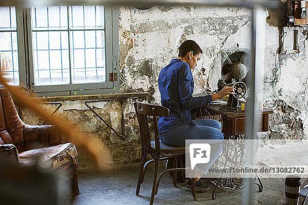Modedesignerin arbeitet in alter Werkstatt an einer Nähmaschine