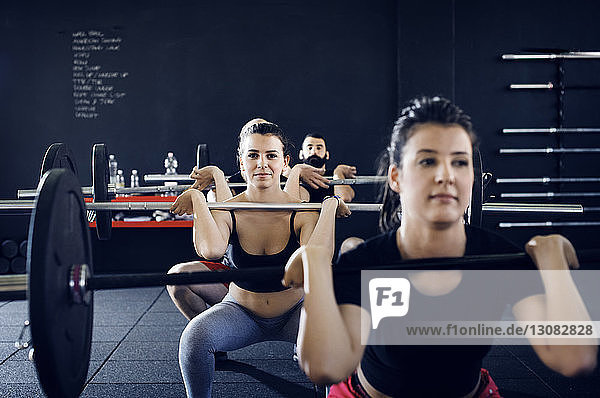 Portrait of confident athletes lifting barbells at gym