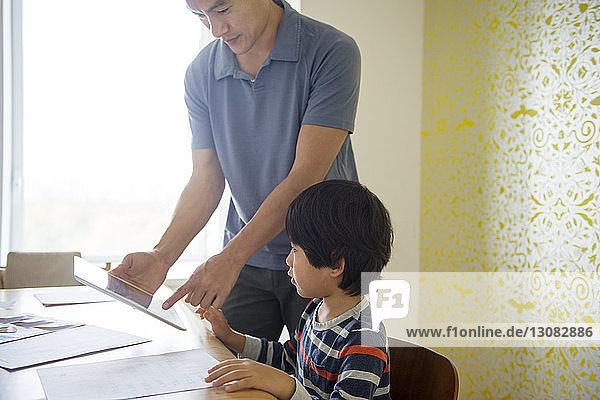 Father showing tablet to boy while assisting in homework at home