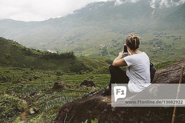 Rückansicht einer Frau  die Landschaft mit einem Smartphone fotografiert
