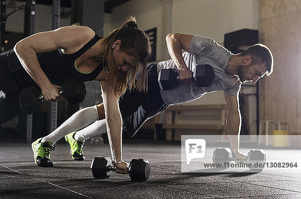 Determined male and female athletes doing push-ups while exercising with dumbbells in gym