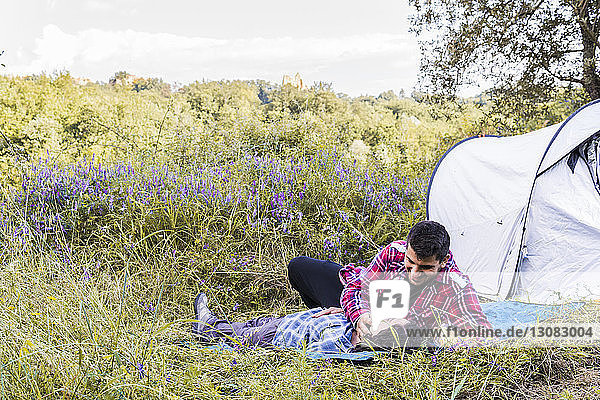 Romantic couple relaxing on blanket at campsite in forest