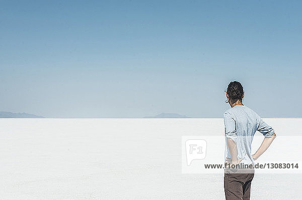 Rear view of man standing at salt flat against clear blue sky