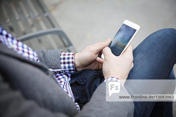 Mittelsektion eines Mannes  der ein Mobiltelefon benutzt  während er im Park auf einer Bank sitzt