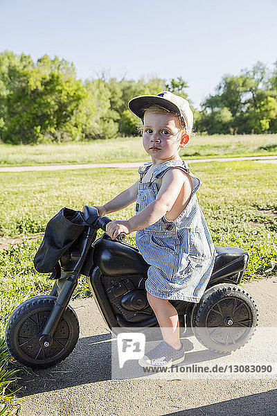 Portrait of cute boy riding toy motorcycle at park