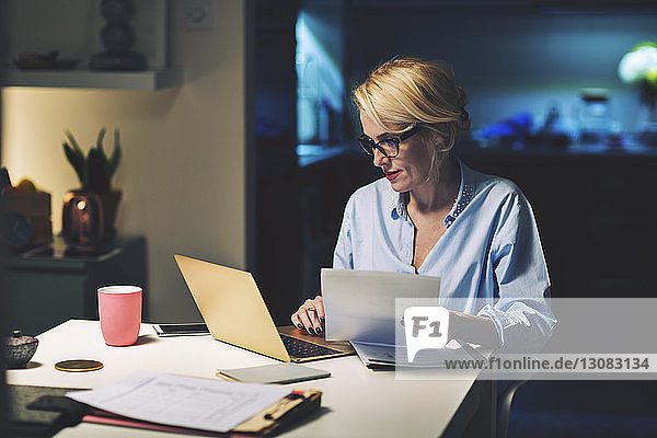 Business woman with document using laptop computer while working at home