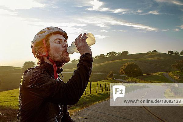 Mann mit Helm beim Trinken von Wasser gegen den Himmel