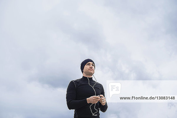 Low angle view of thoughtful male athlete listening music against cloudy sky