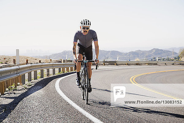 Man cycling on road against clear sky