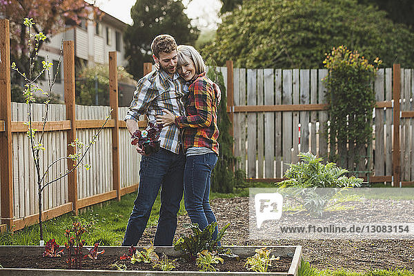 Couple embracing while gardening at backyard
