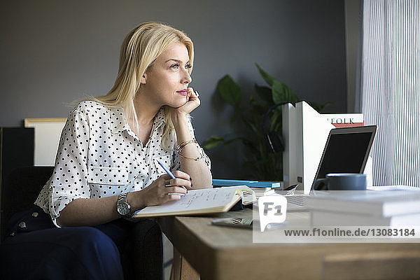 Thoughtful woman looking away while working at home