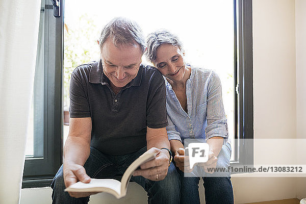 Happy mature woman using smart phone while sitting man reading book at home