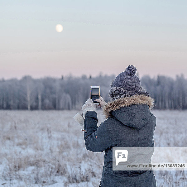 Rear view of woman photographing with smart phone while standing on snowy field during sunset