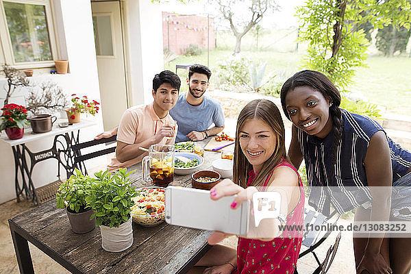 Fröhliche Freunde  die sich beim Mittagessen am Freilufttisch vergnügen