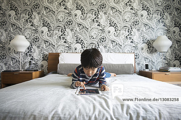 Boy lying on bed and using digital tablet in bedroom