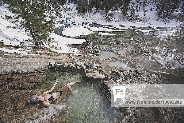 Hochwinkelaufnahme einer Frau im Bikini  die sich im Winter im Thermalbad im Wald entspannt