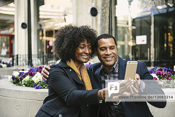 Smiling couple taking selfie through smart phone while sitting on seat in city