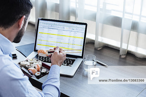 Side view of businessman eating sushi while using laptop on window sill in hotel room
