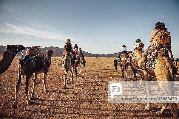 Rückansicht von Touristen  die bei Sonnenschein auf Kamelen in der Wüste gegen den Himmel reiten