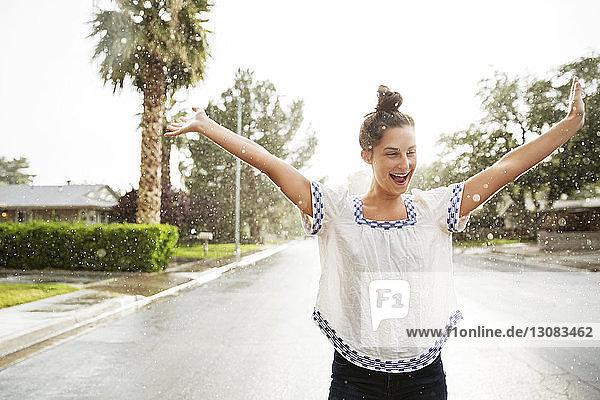 Fröhliche Frau steht mit ausgestreckten Armen auf der Straße