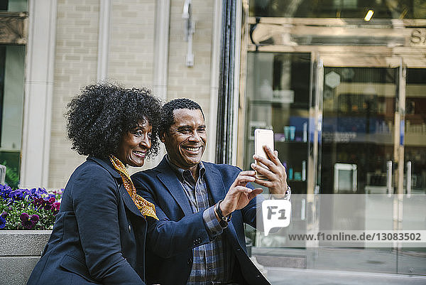 Glückliches Paar  das sich über ein Smartphone selbstständig macht  während es in der Stadt auf seinem Platz sitzt