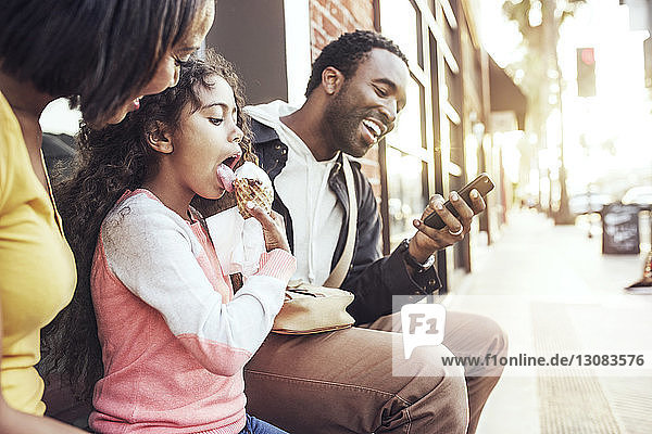 Girl licking ice cream while sitting by parents at sidewalk