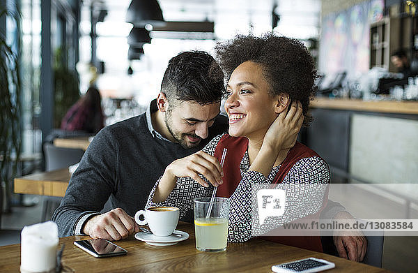 Happy business couple having drinks in cafe