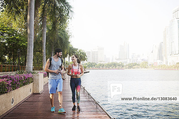 Couple smiling and walking on wooden walkway at riverbank