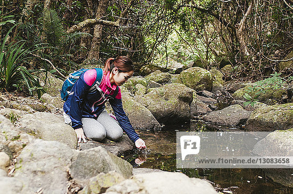Woman drinking water from lake while sitting on rocks in forest