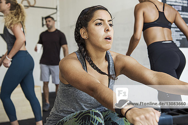 Woman exercising on rowing machine against athletes in crossfit gym
