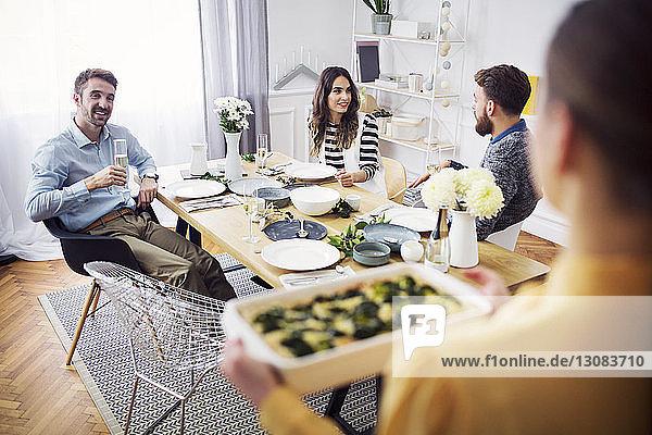 Frau hält Servierteller in der Hand  während Freunde bei Tisch eine Lunch-Party feiern