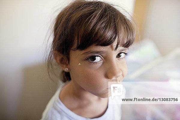 Nahaufnahme eines Mädchens  das im Stehen zu Hause ein Gesicht macht