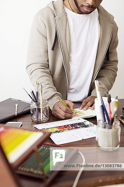 Male illustrator making painting at desk in creative office