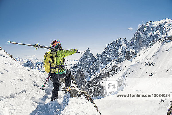 Side view of hiker with skis standing on snow covered mountain against clear blue sky