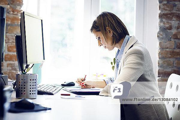 Geschäftsfrau  die mit dem Computer am Schreibtisch im Büro in einem Buch schreibt