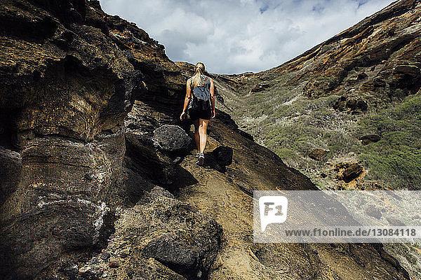Niedrigwinkelansicht eines Wanderers  der den Berg gegen den Himmel besteigt