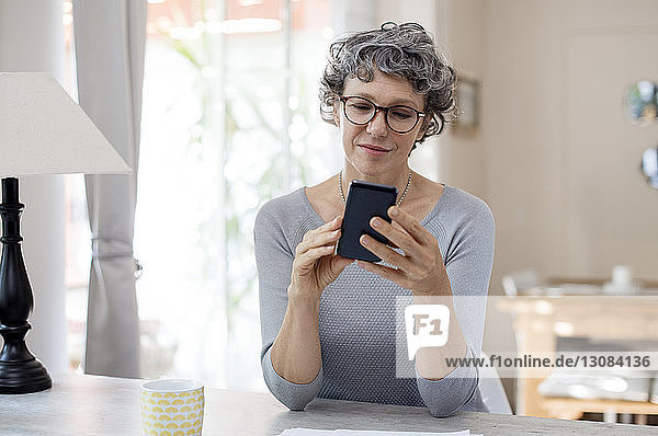 Mature woman using smart phone on table at home