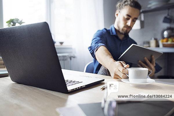 Mann trinkt Kaffee  während er zu Hause einen Tablet-Computer benutzt
